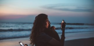 couple hugging and using smartphone near sea on sunset 4555321