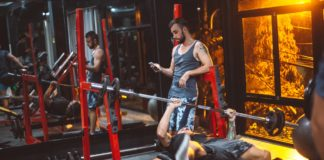 sporty fitness trainer and man lifting barbell 4553611